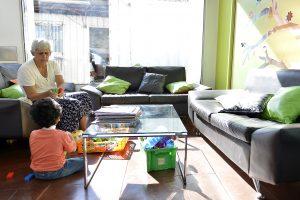 Una abuelita y su nieto jugando dentro de la Sala Familiar Ronald McDonald en Sotero del Rio. Hay varios sofás negros con cojines verdes y naranjados.