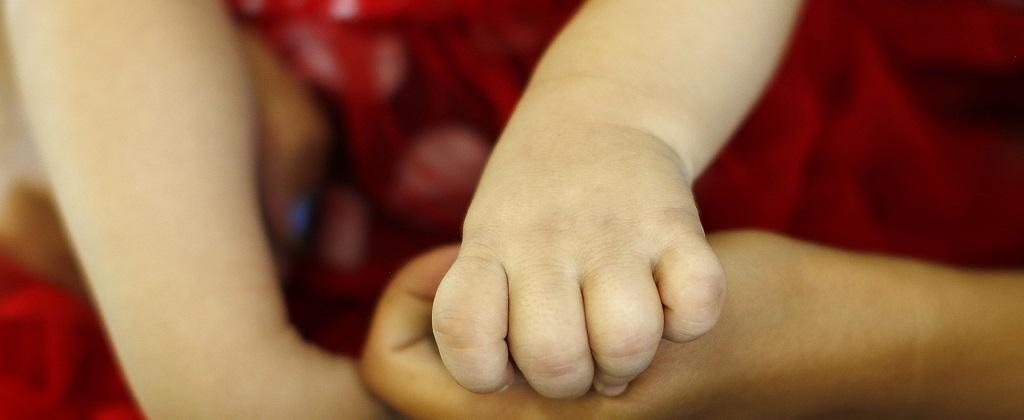 La mano de un bebe se entrélaza con otra mano.
