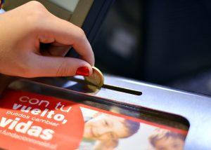 """Una mujer sostiene una moneda antes de depositarla en una alcancía. En la alcancía se lee """"Con tu vuelto, puedes cambias vidas."""""""