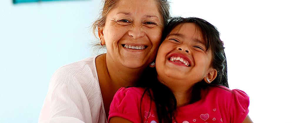 Una niña riendo a carcajadas mientras su abuela la abraza fuertemente.