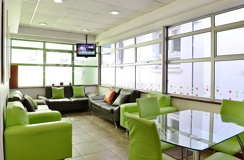 Interior de la Sala Familiar Ronald McDonald en Exequiel Gonzalez Cortes. Se ven varios sofás y una mesa con sillas alrededor. Muchas ventanas.