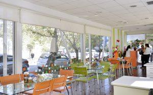 Interior de la Sala Familiar Ronald McDonald en Sotero del Rio. Se ven varias sillas naranjadas y verdes, muchas ventanas y le mesa de recepción donde hay varias mujeres hablando.