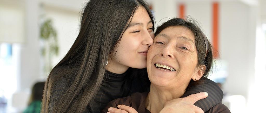 Una jovencita abraza a su abuela mientras las dos sonríen felices.